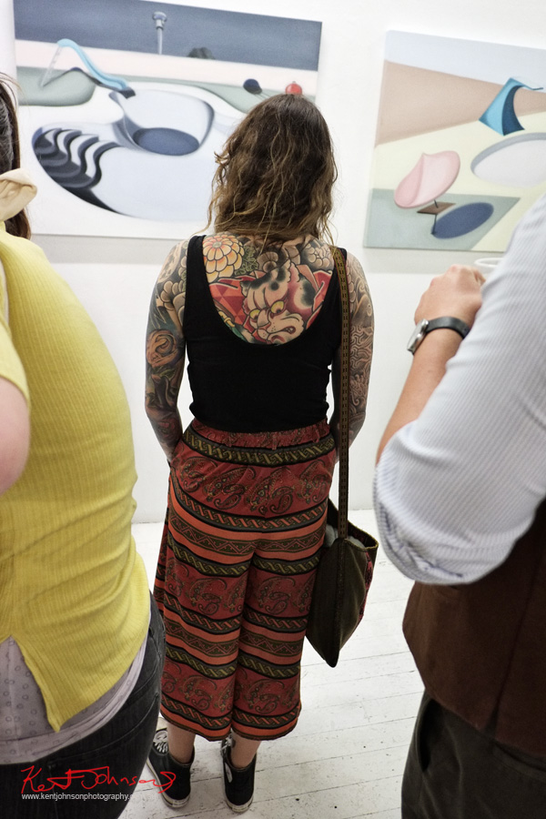 Woman with classic Japanese inspired full back tattoo, full sleeve tattoos, black singlet top, heavily patterned pants, Chuck Taylor All-Stars, at China Heights Gallery Lucy O'Doherty art in the background.