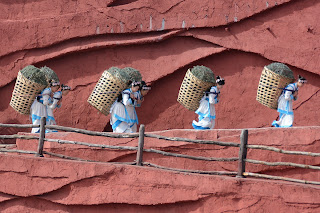 Women carrying baskets on their backs at the Impression Lijiang show