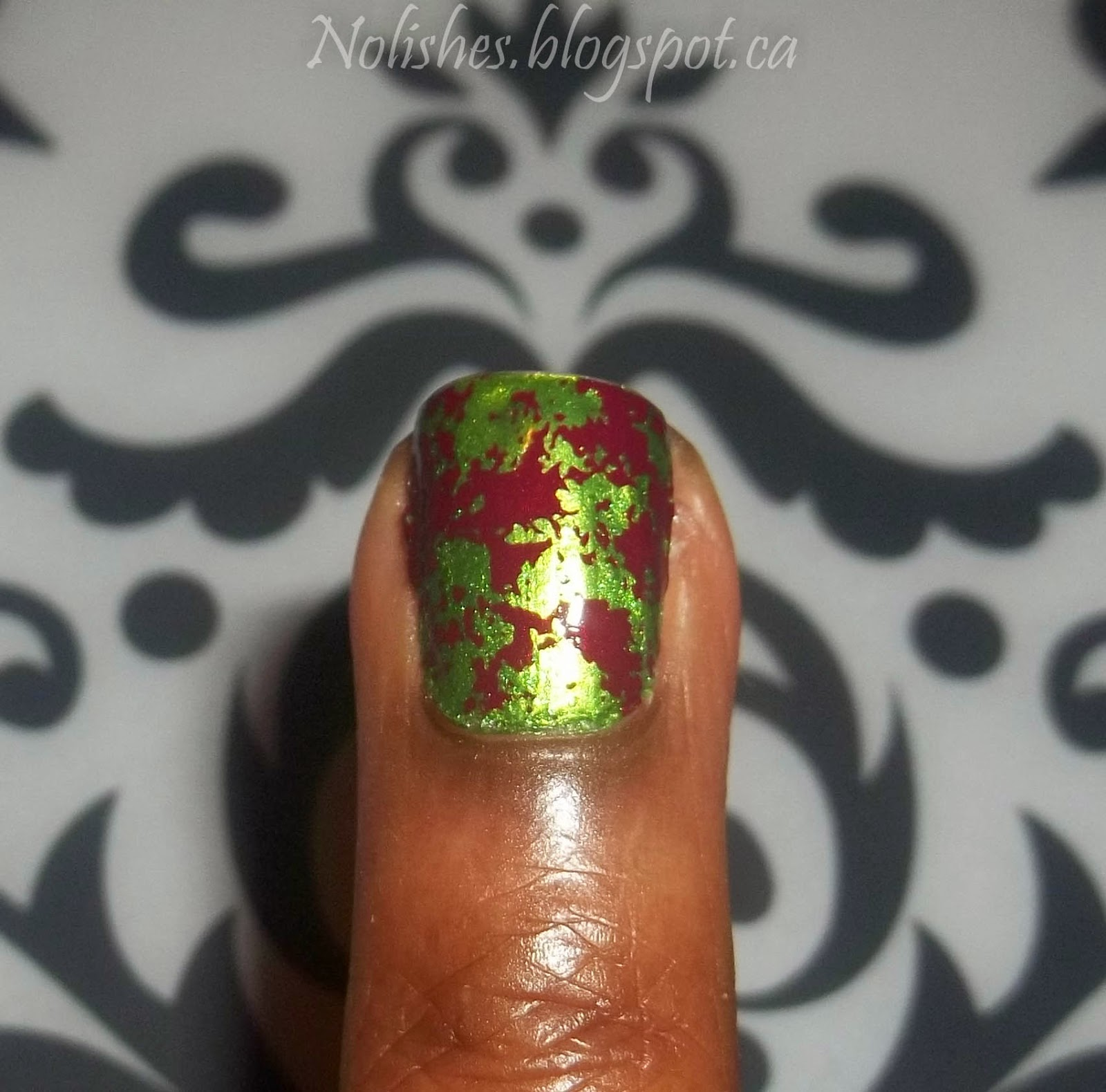 one nail with shimmery green base colour stamped with a splotchy red distressed pattern.