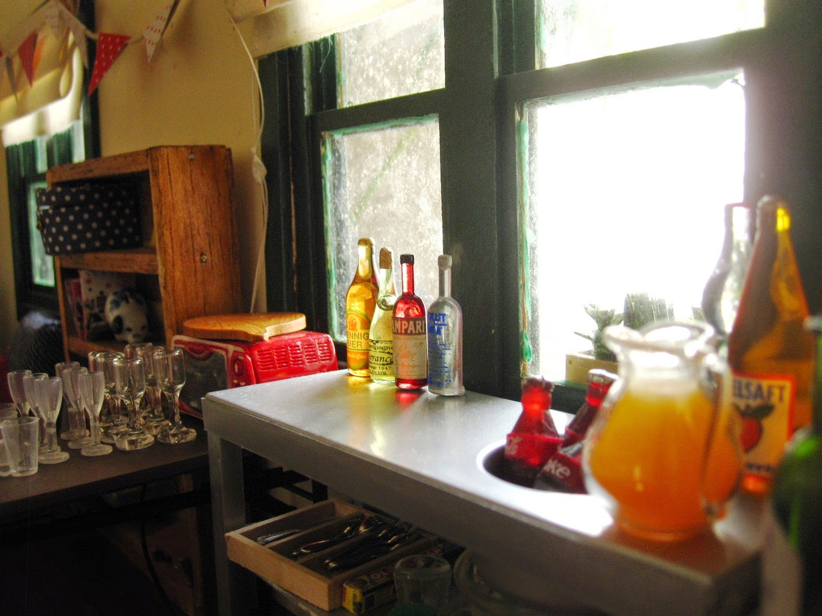 Selection of miniature dolls' house alcoholic and non-alcoholic drinks arranged in a kitchen, ready for a party.