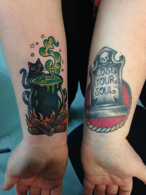 dos tatuaje en antebrazos de gato y caldero de bruja y lapida