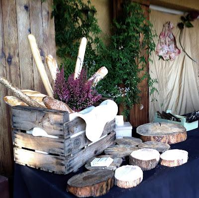 bodegon de quesos hecho con troncos de madera, caja antigua, panes y brezos