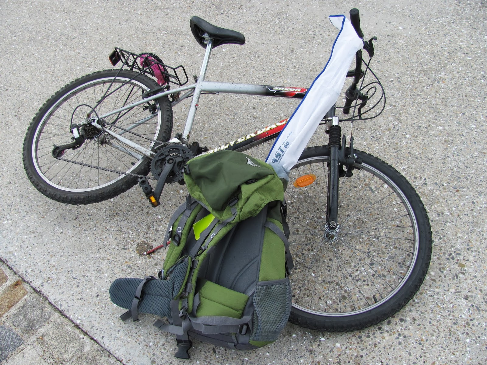 A bicycle is parked with a green backpack containing a fishing rod and fishing kit at Dun Laoghaire, Co. Dublin, Ireland