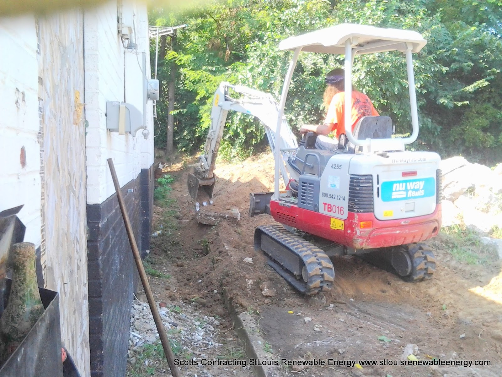 Removing the Existing sidewalk and excavating the dirt using a small track loader- the perfect size for working in confined areas such as this.