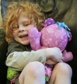 Boy hugging a pink Doodle Bear