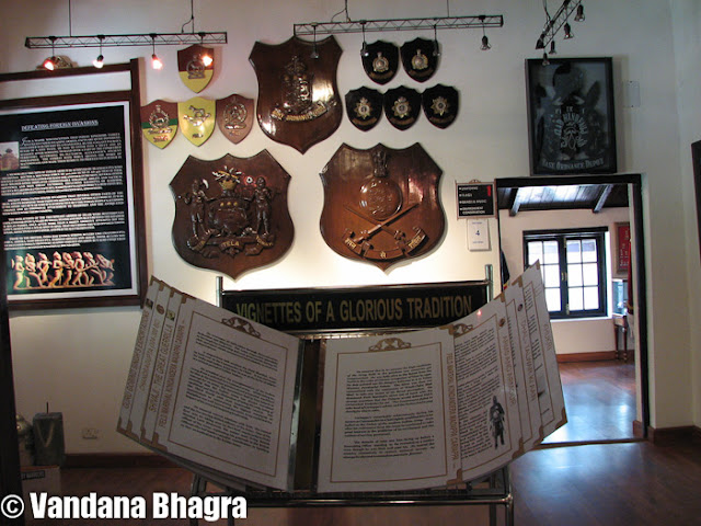 "The Army Heritage Museum: An eye opener to Shimla's history  : Posted by Vandana Bhagra on www.travellingcamera.com : Hidden amidst huge pine trees, as you circle down from Kennedy House passing through Kumar House towards the Annadale Ground the sight of this huge open grass turf is something to be awed.  As you step inside the Ground, a guard posted there will politely guide you towards the Army Heritage Museum which is opened from April to October from 10am-2pm, 3pm-5pm and during winter from November to March from 10am-2pm, 3pm-4pm. The road leading towards the museum is decorative with 25 pounder artillery gun at the entrance, 40mm antiaircraft gun, 100 mm artillery field gun, manicured lawns and landscaped gardens. Inaugurated by former chief minister Virbhadra Singh on September 20, 2006 this museum has been dedicated to the citizens of Shimla by Lt Gen KS Jamwal, but quite sad that very few citizens actually know about this amazing museum.The history of Annadale is associated with the British rule asfrom being a nondescript village, under the Viceroy, John Lawrence, Shimla was officially declared as the Summer Capital in 1864 of the British Empire, a status retained up to India's Independence. Annadale since its inception in the 1930s has been a favourite place for picnic parties, fetes and fancy fairs, birthday balls, flower and dog shows, races, gymkhanas, polo and other tournaments hosted by the army. The race course dates back to 1840 and Sir Mortimer Durand inaugurated the first football tournament in 1888, which was later moved to Kolkata. Regular military activities have ensured upkeep of this place as its pristine glory amidst the sylvan surroundings is still immaculate. As you walk towards the main building huge stone planks with details of state heroes and their alma mater since 1947 can be seen. A historic note on Himachalis and their ancient linage dating back to the Aryans, who are renowned for their military valour, chivalry, traditions and politeness and were primarily recruited into the ogra Regiment of the Indian Army stands tall. As one of the planks reads, ""This Museum is about the Indian Army and its soldiers, their virtues, loyalty to comrades, fidelity to an oath, courage under stress, about their mind set and military thinking, passed down from generations for over 5000 years; about regiments and the intense regimental pride which they so passionately treasure, about Indian Captain of war and their contribution which make an Indian proud"".As you step inside the main building you feel dwarfed by the humongous wall hung boards depicting the army as well as Indian history. Be it the army ethos, ancient military psychology, ancient military thinking, Mahabharta, Ramayana or the Chandragupta period, history of armies of medieval India or the first was of Independence it is all out there to be read and wowed at. It is just not a history lesson read out of books, it is like reliving it all over again. The experience is so thrilling that once you begin to read it you feel quite educated as wll as entertained. On entering the room as you walk to the left you can see a huge stone soldier dressed as a warrior and the types of helmets they wore. The wall right next to it is adorned with awards and accolades won over a period of time. Another left turn towards the next room you can see mannequins in uniforms worn during the British rule, a note on evolution of these uniforms, shoulder titles and cap badges of armoured corps. The following room towards the right takes you to the musical instruments played by the army band displayed immaculately. Walking straight ahead you can read about all the conservation efforts undertaken by the army and how Major General Thomas Hardwicke set the trend for collecting specimens of birds, mammals, insects, reptiles, nests and in due course more than a dozen were named after him. He finally bequeathed his entire collection and paintings to the British Museum, London which became the first ever comprehensive display of Indian Natural History in the world in 1820. Theinstinctive reverence and love for weapons will take you the next room where arms and ammunitions are kept. Each assault rifle or shotgun is clearly labeled for military and young enthusiasts who wish to enrich their knowledge about what was used during the pre-and post Independence era, though what's missing are the exact dates. The wall is beautified with different kinds of axes used in action. The anti tank grenade launchers, pistols, rocket launchers, gun machine are all neatly stacked on the table with details about their city of origin. Next to this table an array of bows can be seen hanging from the wall which was used by the infantrymen made as per the length of a man. The shields, swords and knives dating during 1900's can all be seen hung on the wall in all their shine and gleam. The armour embellished with priceless gems, gold and silver was significantly made as stress was laid on the fact that it was an essential element of war. The six horses driven carriage along with the cannon gun is a pece f art beautifully carved. Walking out into the main room after taking a full circle you are enlightened with a chronology of military events dating 2000 BC up to October 2002. Chiefs of Indian Army during the pre-Independence era starting January 1748 with Major Stringer Lawrence to General Sir Rob Lockhart  till November 30, 1945 are listed on a huge board along with the names of chiefs post-Independence dating August 15, 1947, General Sir Rob Lockhart till date as General VK Singh who took over in April 1, 2010. In a glass cupboard on one end, you can see the Field Marshal's Baton and various kinds of 'khukuri's' (Nepalese knives) and a miniature statue of Maharana Pratap on his horse.  Once out of the main hall there is another room full of army combat badges which are given to personnel, an area prohibited from photography. But just standing in the room it had an awe inspiring effect, a feeling what it means to be a soldier is suddenly instilled. The surrounding environment park is equally amazing with atleast 40 different kinds of cactuses planted in the green house, the clean manicured lawns, models of dears and bears around the park and iron-made 'machans' add further interest to the place.Behind the main building as you walk around the green house you can see the awesome, pristine Annadale Ground where army personnel can be seen playing golf. Turn right and you walk into the room full of honours and awards, ""This section of the museum is dedicated to those valorous men and women to whom we are beholden"", as the writing on the wall states. The next room outlines the landmarks of Shimla starting from 1813 up to 2006. The walls have old photograph of Shimla and miniature models of some famous heritage buildings such as the Viceregal Lodge, now known as the Indian Institute of Advance Studies, the Gorton Castle now the AG Office, Ellerslie or the present Secretariat, the Bishop Cotton School and many more. Photographs of horse driven carriages, the Shimla Kalka toy train, old images of The Mall, Old Post Offce, Scandal Point and Lakkar Bazar will all carry you back to the 1900's Shimla.The Conference Hall on the other end of the Museum will give you a feeling of what it's like being in a commanding position. Displayed history of infantry regiments will equally enrich you. Moving out you can see the walls decorated with the badges of armoured corps, which traces its origin in the Indian Cavalry as some of the older regiments were formed in 1773. The twelve armoured regiments that were apportioned to the Indian Army in 1947 have grown to the present strength of 60 regiments, whose badges are now mounted on the walls. The Army Heritage Museum is a treasure house of culture and history but unfortunately the army authorities/personnel in charge are reluctant to share dates and exact reasons that have made our history so rich and important. It would have been much better if the army authorities were to engage professionals to give a guided tour of the entire Annadale complex and the museum which is being perfectly mantained by them. But despite this fact a walk around the complex is fun, entertaining and very educative."