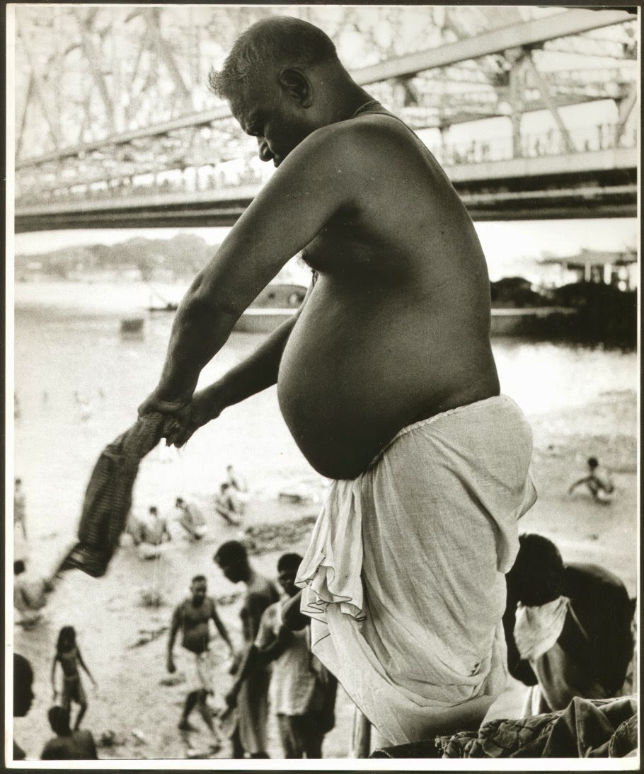 A Man is Wringing Out his Towel after bath in River Ganges (Ganga) in Kolkata (Calcutta). Howrah Bridge (Rabindra Setu) is visible in background - c1980's