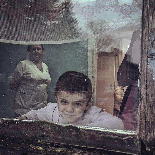 φωτογραφία που απεικονίζει το πρόσωπο ενός παιδιού μέσα από ένα παράθυρο ενώ στο βάθος διακρίνονται 2 ενήλικες