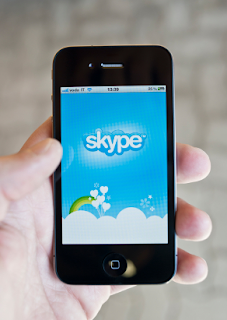 someone holding a iPhone displaying Skype