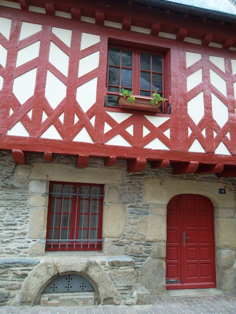 Red and white half timbered and stone clad traditional Breton house in Josselin Brittany