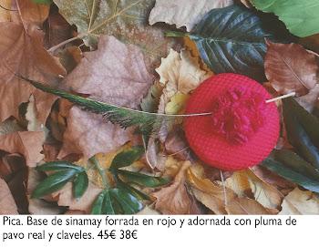 Tocado de base sinamay forrada de rojo con pluma de pavo real y claveles