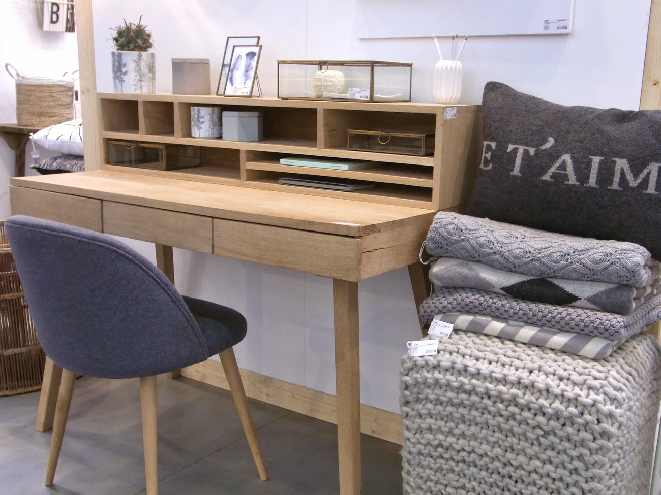 Holzschreibtisch, Schreibtisch Holz geradlinig, Stuhl gepolstert grau, Kissen, gestrickte Poufs, Plaids, Decken grau weiß, geometrische Muster