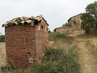 El Pou del Mas Mitjà amb la masia a la seva dreta