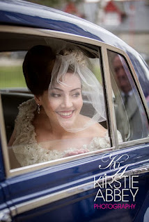 Bride in her blue vintage car wearing a bespoke hand made headdress and veil with vintage hairstyle