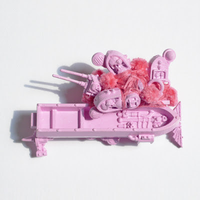 This brooch is constructed out of Warhammer pieces, painted with pink nail varnish and adorned with thread and pink pom poms.
