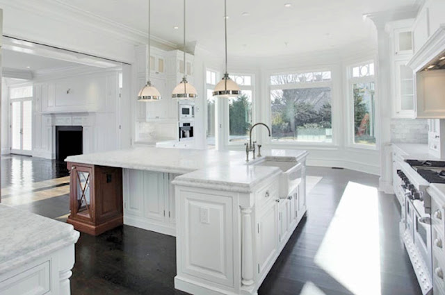 alternative view of the kitchen with hardwood floors, white marble counters, stainless steel appliances, white cabinets and a huge island with pendant lights