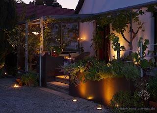 Die Beleuchtung zaubert abends eine kuschelige Atmosphäre in den modernen Garten