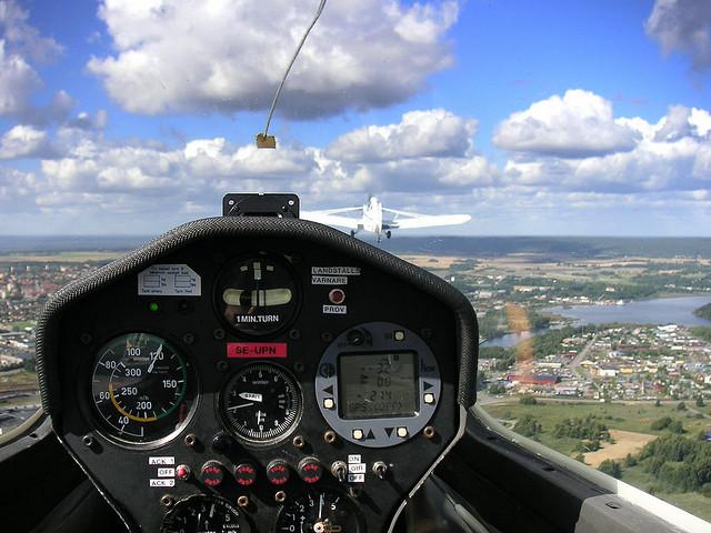pohled do krajiny z pozice pilota přes budíky letadla