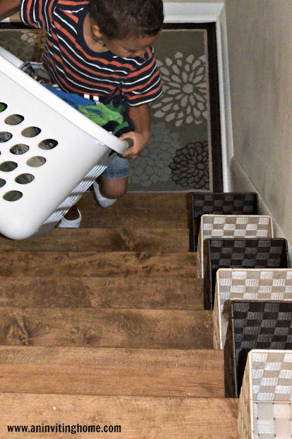 kids carrying their own laundry up the stairs