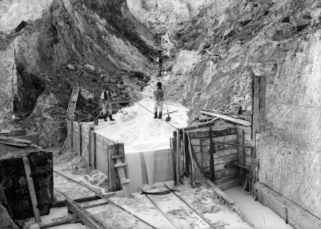 Lantern China-clay Works, near Rescorla, St. Austell. Looking SW. View of lower part of clay-pit. This photograph, taken down in the pit, shows the stream of water, by which the clay is washed out of the decomposed granite travelling down the stope and from thence through the sand-pits to the 'bottom hole launder', whence it is pumped to the surface. The sand-pits are only partly visible in the photograph, but the annexed diagram shows the direction of flow of the water.