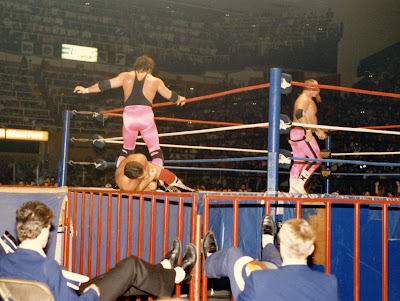 Maple Leaf Gardens ushers have their feet up on the ringside railing and their hats in their laps as Brett Hart stomps Raymond Rougeau on the MLG ring ramp.