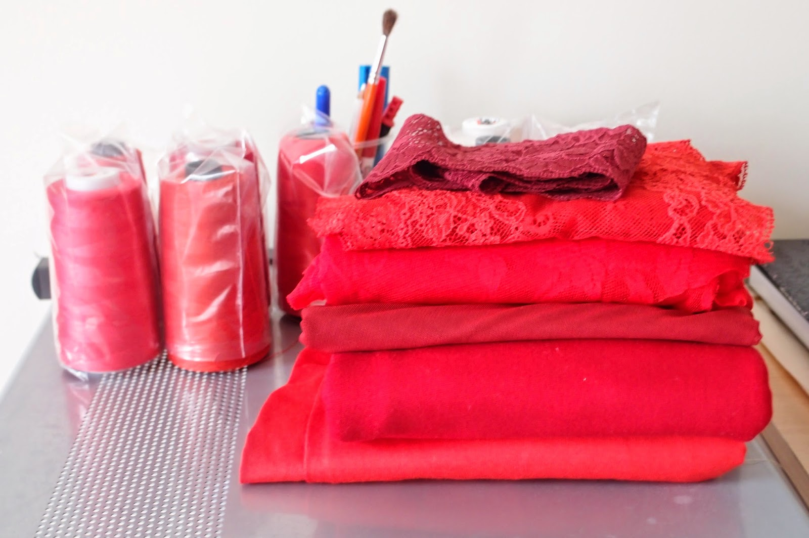 red lingerie fabrics and laces on my sewing table