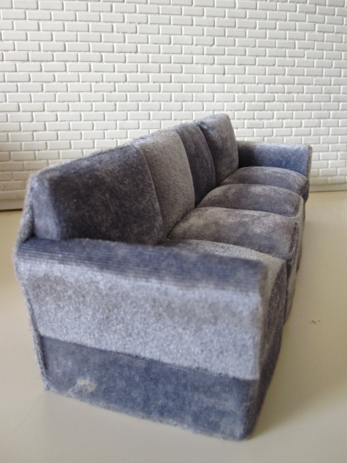 Modern miniature four seater grey velvet sofa.