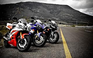 Drie motoren op een rij langs de weg met bergen