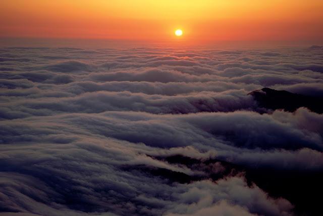 Preciosa puesta de sol, vista por encima de las nubes