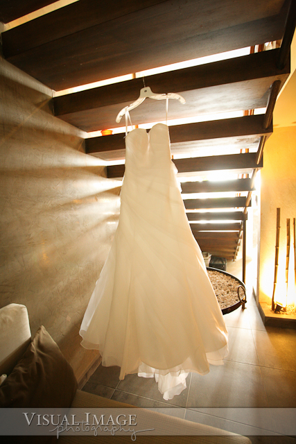 Wedding dress hanging under stairs with beautiful window light creating shadows on wall