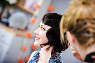 girl getting ready on the wedding morning having her hair styled into glam vintage waves
