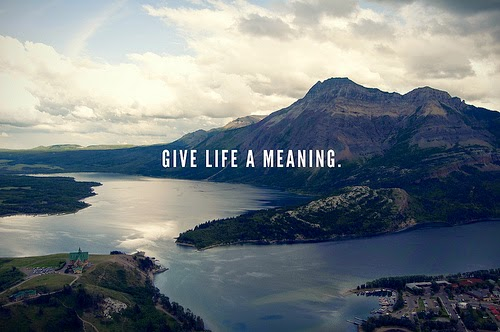 "The quote ""give life a meaning"" with a beautiful mountain, island, and beach as a backdrop."