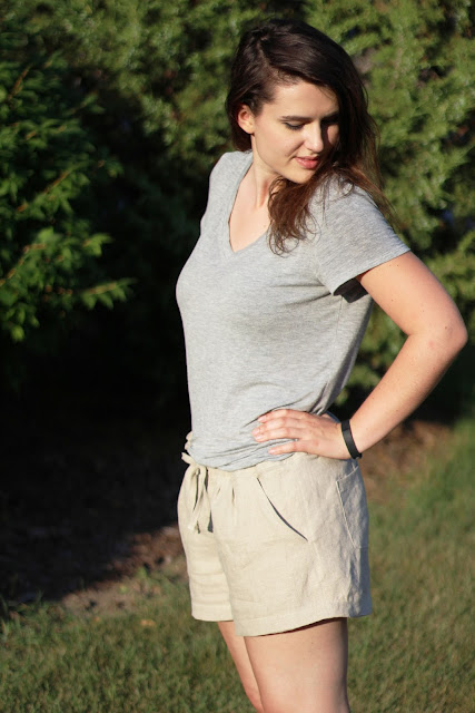 Brunette girl modeling tan linen summer shorts with gray tshirt