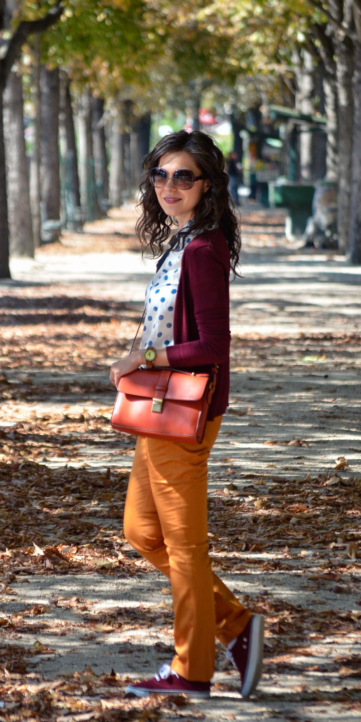 preppy fall outfit in Paris mustard pants burgundy sweater sneakers H&M orange satchel bag dotted shirt blue dots black bow tie champs elysees jardin de tuileries eiffel tower