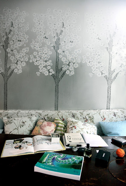 Dining area doubles as a reading space with grey wallpaper depicting trees, floral bench seating and comfy accent pillows