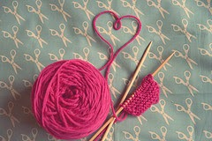 image pink ball of wool with heart formed by wool and stitches cast on knitting needles