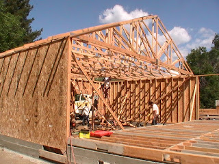 The garage is framed with the roof trusses in place and the subfloor framed