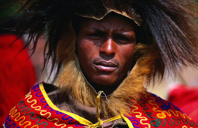 Addis Ababa - Portrait of jousting competitor at festival of Timkat, dressed in style of traditional Abyssinian warrior, with Gelada monkey headdress and embroidered cloak
