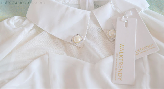 Close-up of the delicate rhinestone and pearl embellishment on the pointed fold-over collar of this WalkTrendy white dress.