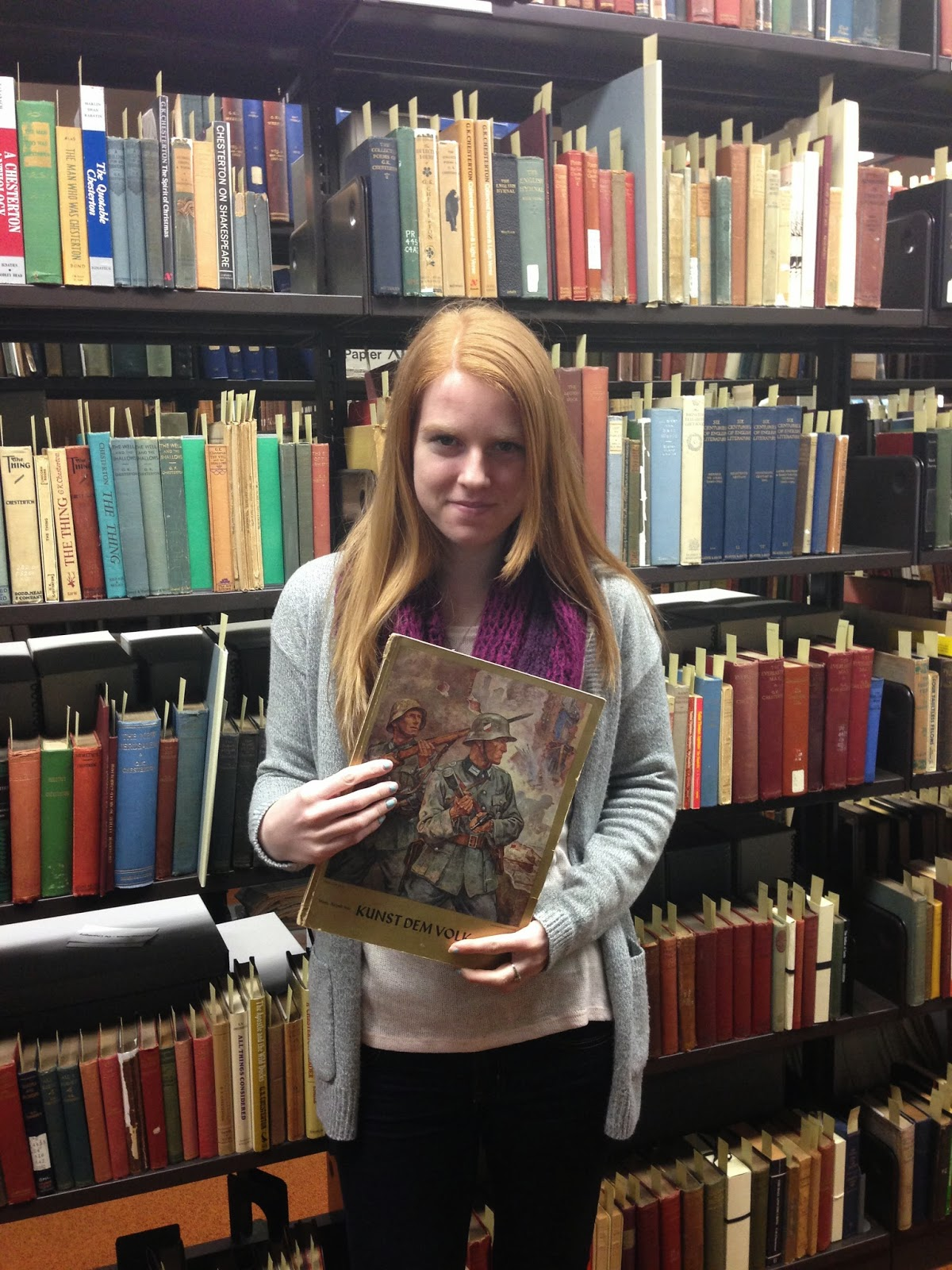 Janine in the Rare Books Room at the Kelly Library posing with an issue of Kunst Dem Volk.