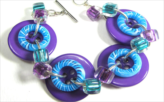 Bold bracelet has big purple buttons accented with donut beads and smaller shiny beads