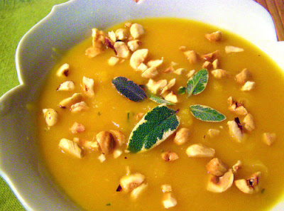 A bowl of smoother, more pureed soup garnished with nuts and sage