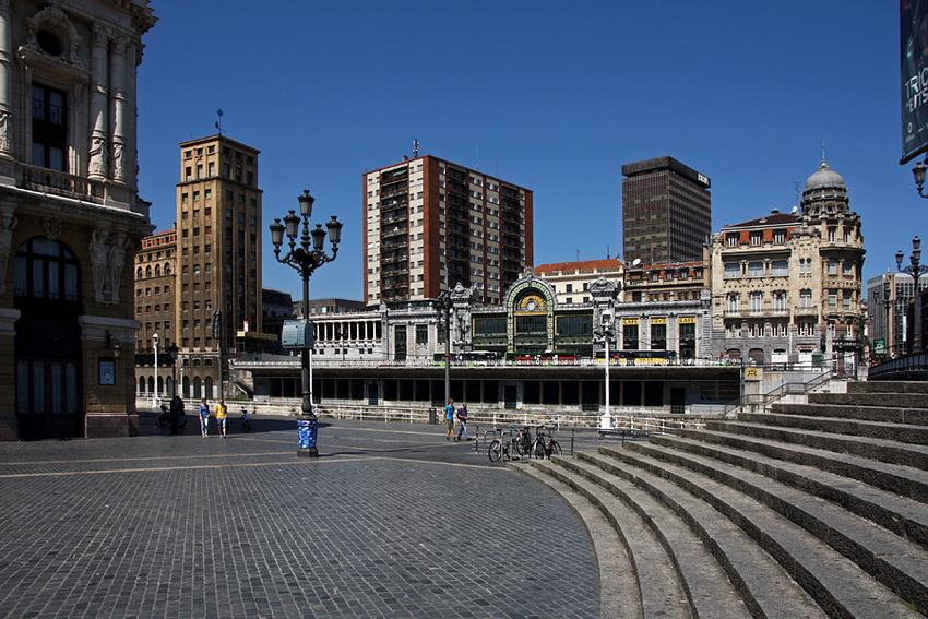 Vista sobre a praça, com um candeiro no meio e algumas pessoas a passar. Ao fundo, contra o cé azul, vários edifícios em altura e um baixo, na frente: a estação do comboio