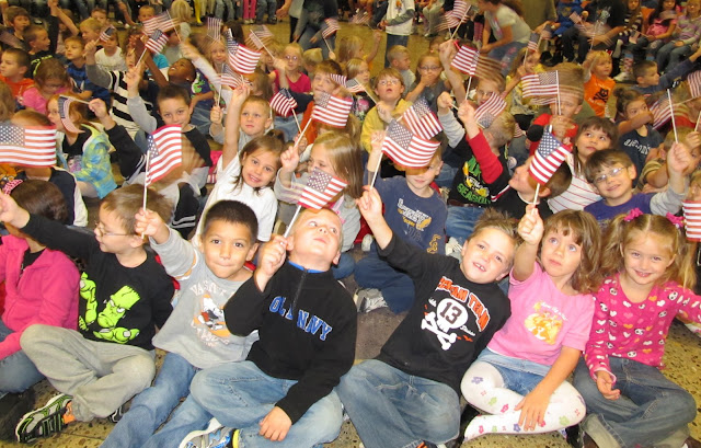 photo of: Elementary School Children Waving the American Flag for Author Visit with Debbie Clement