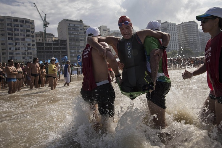 70 Of The Most Touching Photos Taken In 2015 - Paratriathlete Krige Schabort of the United States, is carried out of the water as he competes in the men's Paralympic Triathlon test event in Rio de Janeiro, Brazil.
