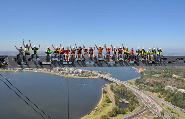 A bunch of construction workers standing on the steel beam high in the air on top of the skyscraper