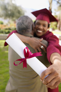 Mature female graduate with diploma hugs a mature man.