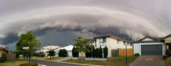 Eye-like storm cloud in background, houses in the forefront
