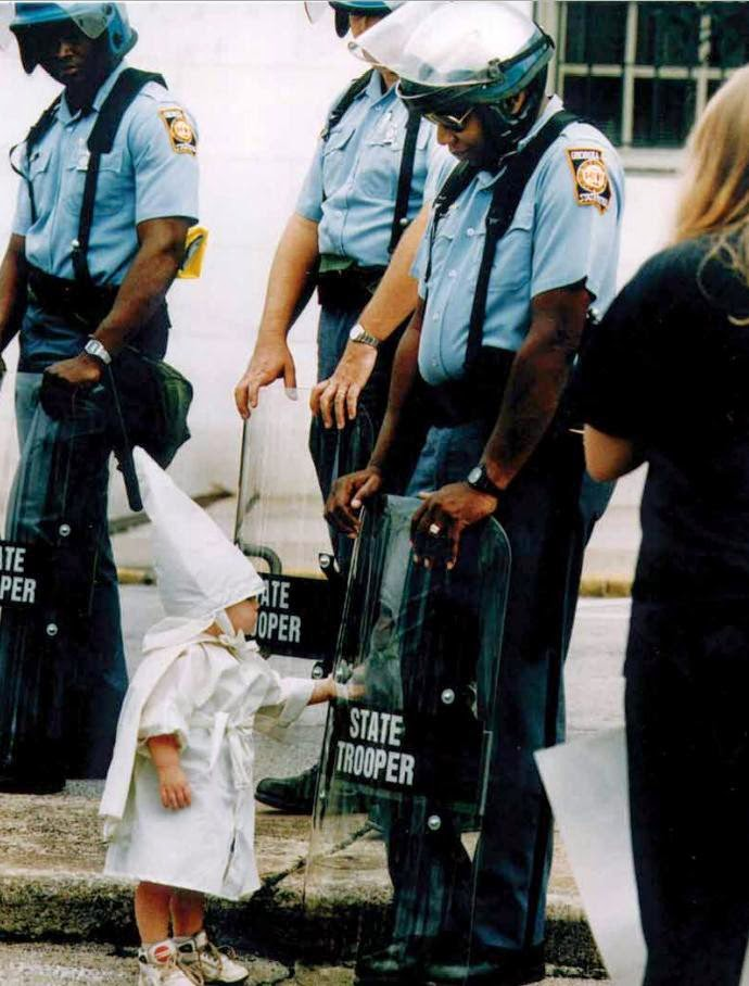 35 moments of violence that brought out incredible human compassion - child touches his reflection during a kkk demostration