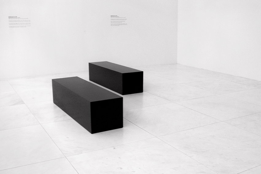 Pormenor de uma exposição: uma sala banca, apenas com dois paralelipípedos enormes e escuros deitados no centro